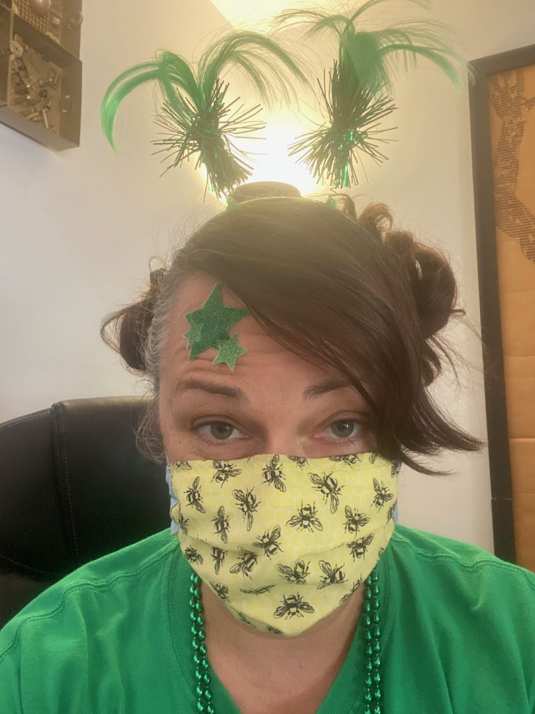 Photo of Lisa Bohn from the end-of-year celebration, wearing a cloth face mask and green fuzzy pigtails on a headband